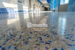 The Grain Valley High School entrance hallway features Bomanite Modena SL custom polished concrete that contains two shades of vibrant blue glass aggregate and eye-catching pieces of sparkling mirror glass and this unique flooring surface was polished to a brilliant luster to display the school's colors and team spirit.