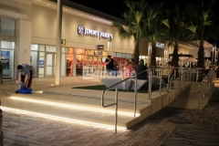 A distinct and durable finish was created here using Bomanite Alloy with seashell exposed aggregate and the resulting decorative concrete step plaza and handicap ramp are the perfect accent to the beach-industrial aesthetic styling at the Tanger Outlets in Daytona Beach, FL.