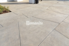Beautiful texture and variation were added to this courtyard area by installing Bomanite Sandscape Refined Antico architectural exposed concrete and the hardscape perfectly complements the surrounding landscape and buildings.