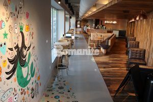 Reverse view through store of artwork on the wall and the decorative concrete floor of Bomanite Custom Polishing System with Modena SL installed by Bomanite Licensee Musselman & Hall in a Starbucks in the Brookside neighborhood of Kansas City.
