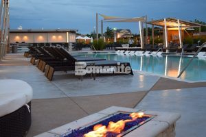 Foreground shows edge of firepit with pool and lounge chairs at the Hard Rock Casino in Tulsa, OK, where Bomanite of Tulsa installed Bomanite Exposed Aggregate Alloy decorative concrete.