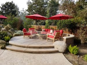 Raised gathering area including a firepit and decorative concrete using the Bomanite Exposed Aggregate Antico Process System at a backyard oasis in Fresno, CA, installed by Heritage Bomanite.