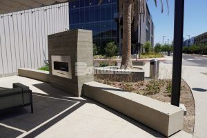 Seat wall with fireplace and seatting area at Flight At Tustin Legacy in Tustin, CA, featuring Bomanite Revealed Exposed Aggregate decorative concrete landscapes installed by Bomel Construction.